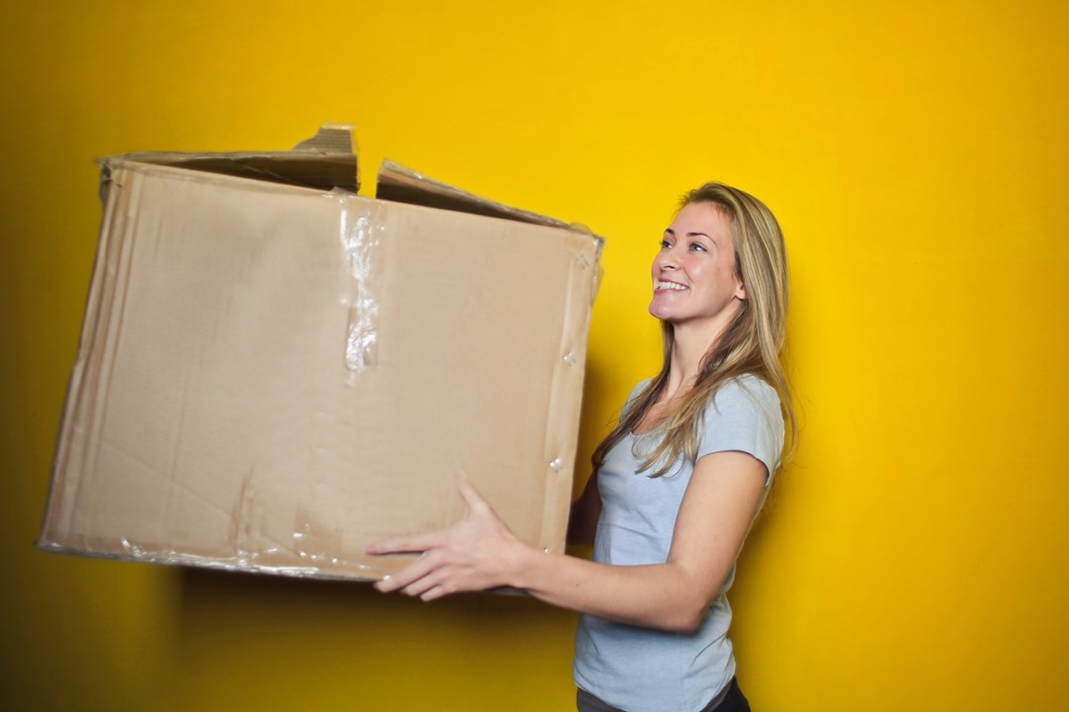 Woman holding box while moving