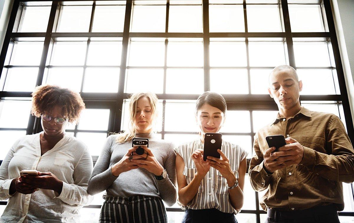 4 people using social media on smartphones