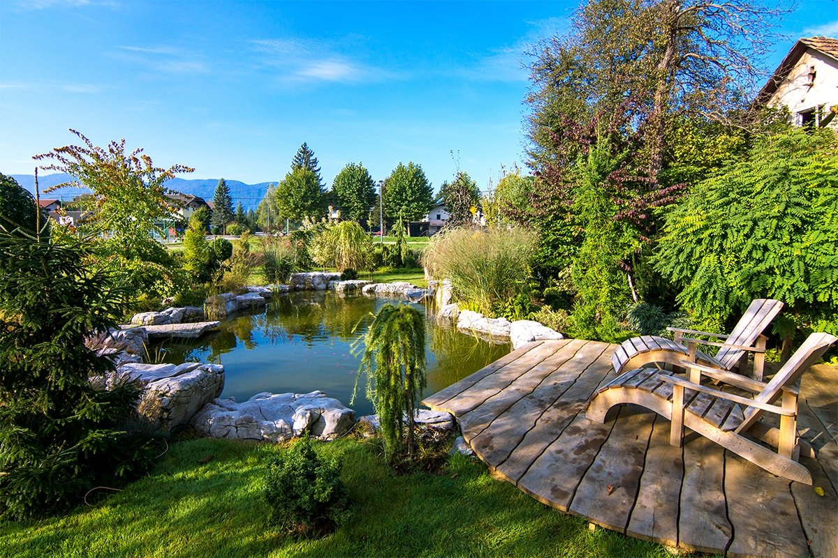 Backyard pond with wooden chairs