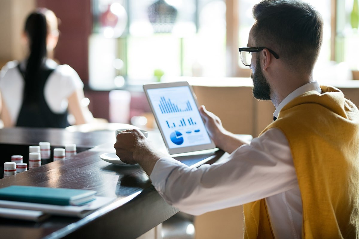 Man viewing digital marketing campaigns on iPad