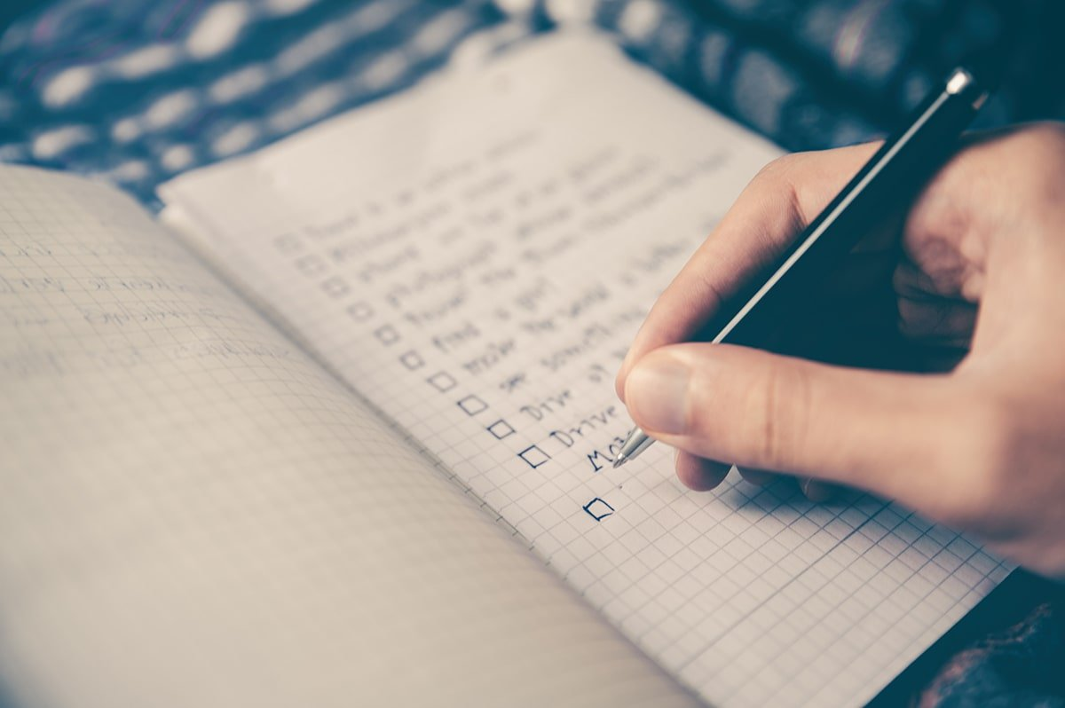Person writing list in notebook